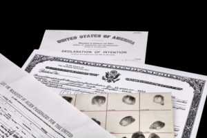 Certificate of US Citizenship, fingerprint card, Declaration of Intention and Passenger Manifest documents isolated on white