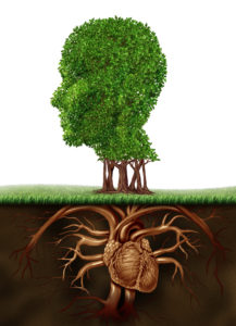 Organic living and healthy lifestyle concept with a tree in the shape of a human head and roots in the form of an anatomical heart organ representing a vegetarian life eating vegetables and fruit for a growing body.