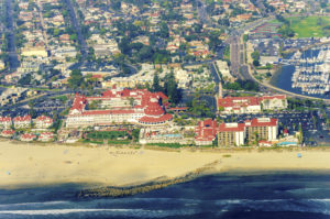 Aerial view of the Coronado island and in the San Diego Bay in Southern California, United States of America. A view of the Skyline of the city, the pacific ocean and the historic Hotel Del Coronado.