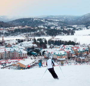 Mont-Tremblant, Canada - February 9, 2014: Skiers and snowboarders are sliding down the main slope at Mont-Tremblant. Mont-Tremblant Ski Resort is acknowledged by most industry experts as being the best ski resort in Eastern North America.