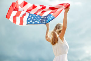 country, patriotism, independence day and people concept - happy smiling young woman in white dress with national american flag outdoors