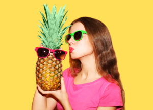 Fashion portrait pretty woman and pineapple in sunglasses over yellow background