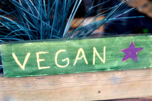 A sign advertising vegan food in a shop window