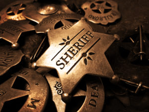 Sheriff's tin badge in pile of star law enforcement badges