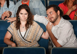 Girlfriend annoyed with rude man in theater