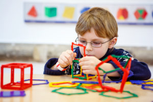 Little kid boy building geometric figures with plastic blocks